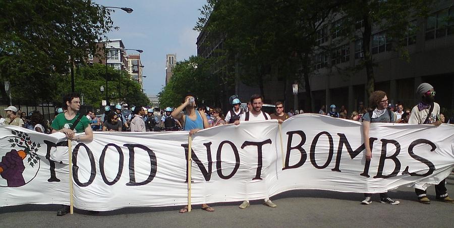 Protesterier halten ein Transparent mit der Forderung 'FOOD NOT BOMBS' hoch - Foto: © 2012 by Lucas Wirl